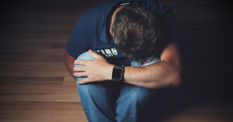uomo triste e depresso seduto sul pavimento